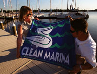 Two people holding up the Clean Marina flag