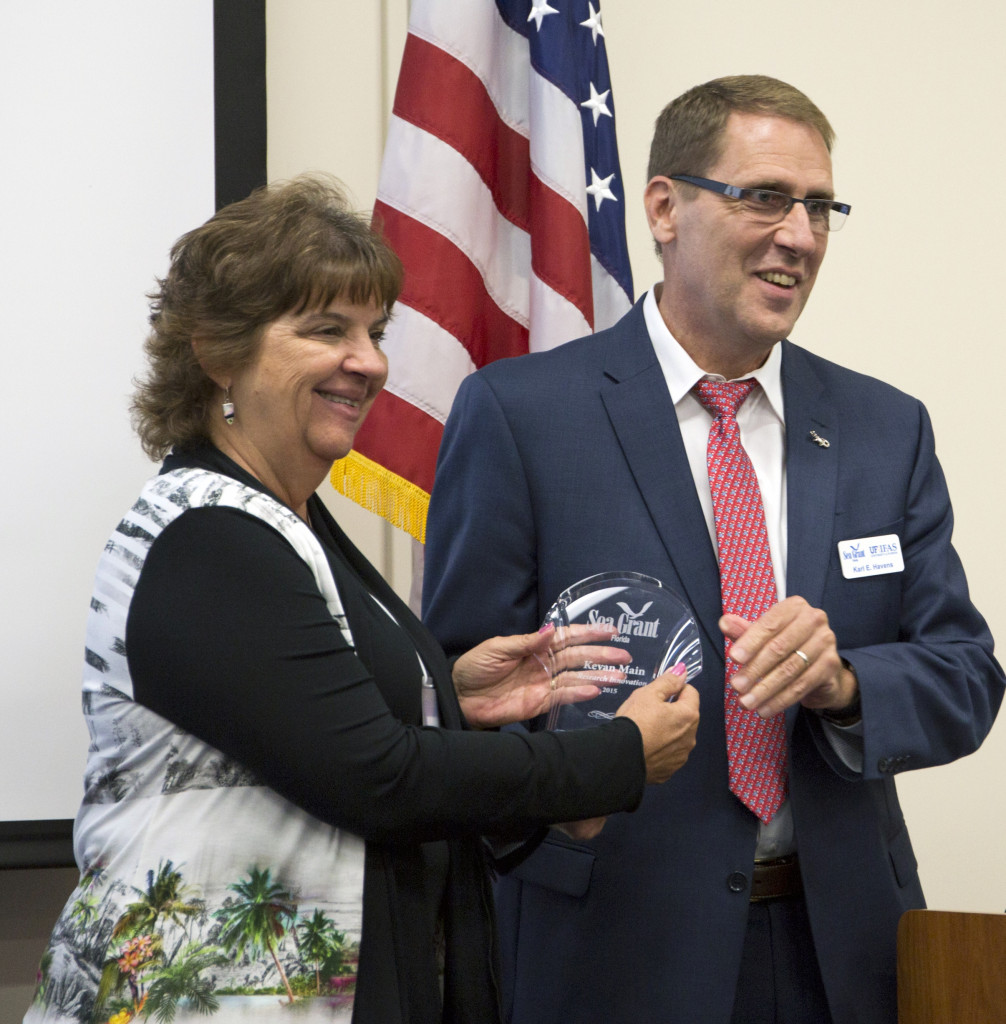 Florida Sea Grant director Karl Havens presents Kevan Main with the 2015 Florida Sea Grant Research Innovation Award.