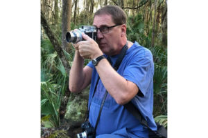 Karl Havens in a blue shirt using a camera