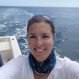Joy Hazell in a boat wearing white shirt, scarf, with blue ocean behind her